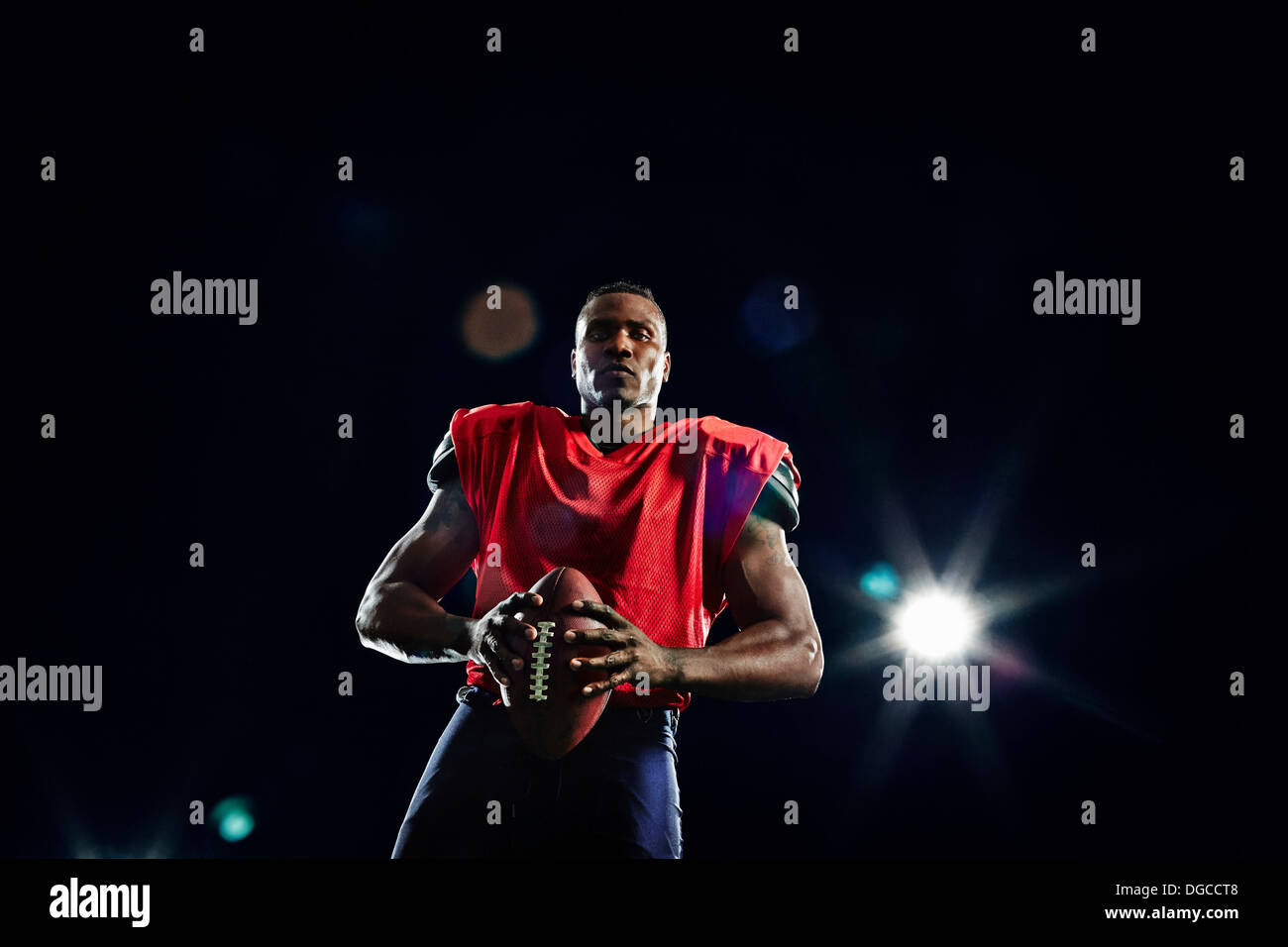 Portrait of american football player with ball - Stock Image