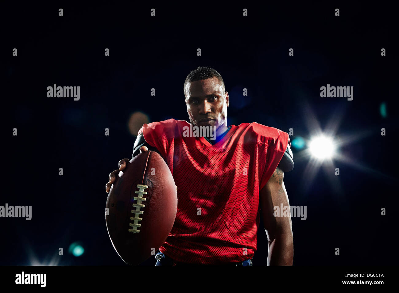 Portrait of american football player holding ball - Stock Image