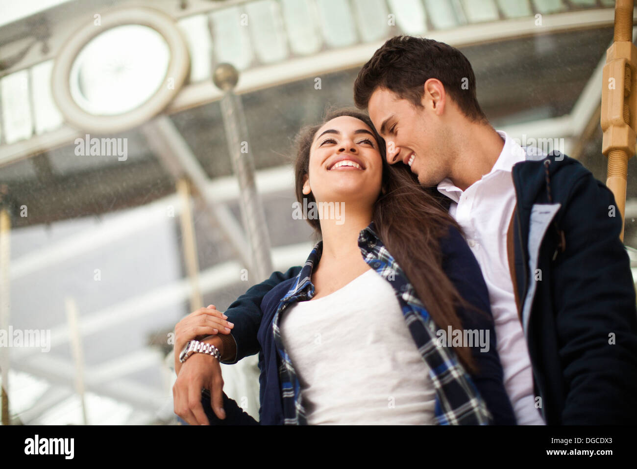 Young man with arm around woman, smiling - Stock Image