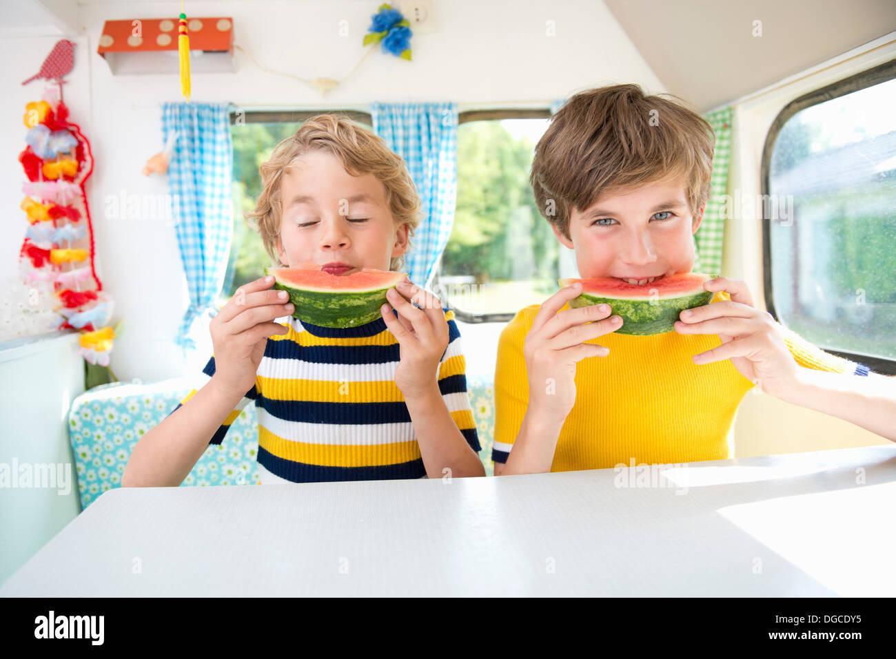 Boys eating watermelon in caravan, portrait - Stock Image