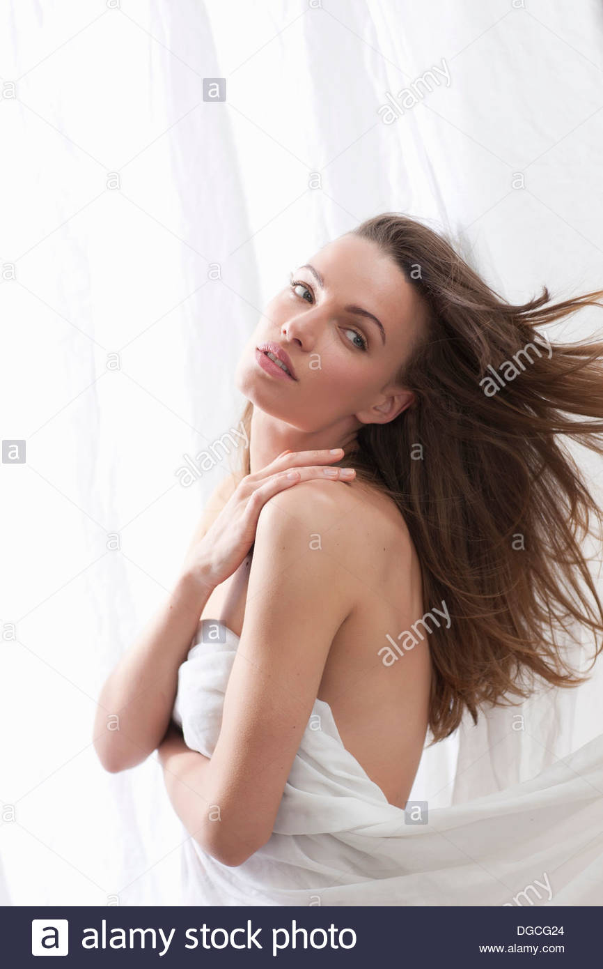 Young woman wrapped in sheet looking over shoulder - Stock Image