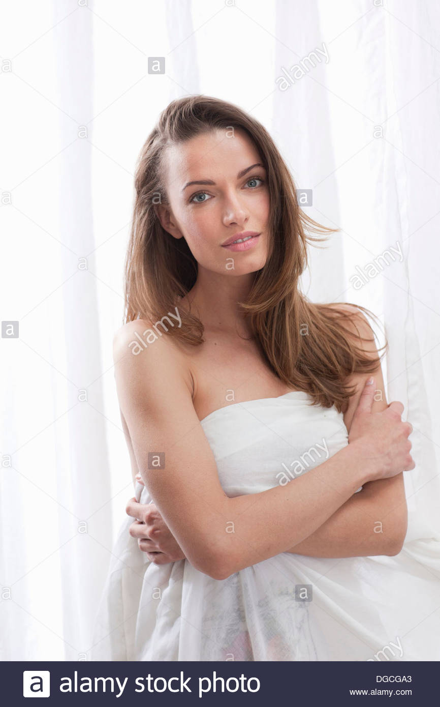Young woman wrapped in sheet, portrait - Stock Image