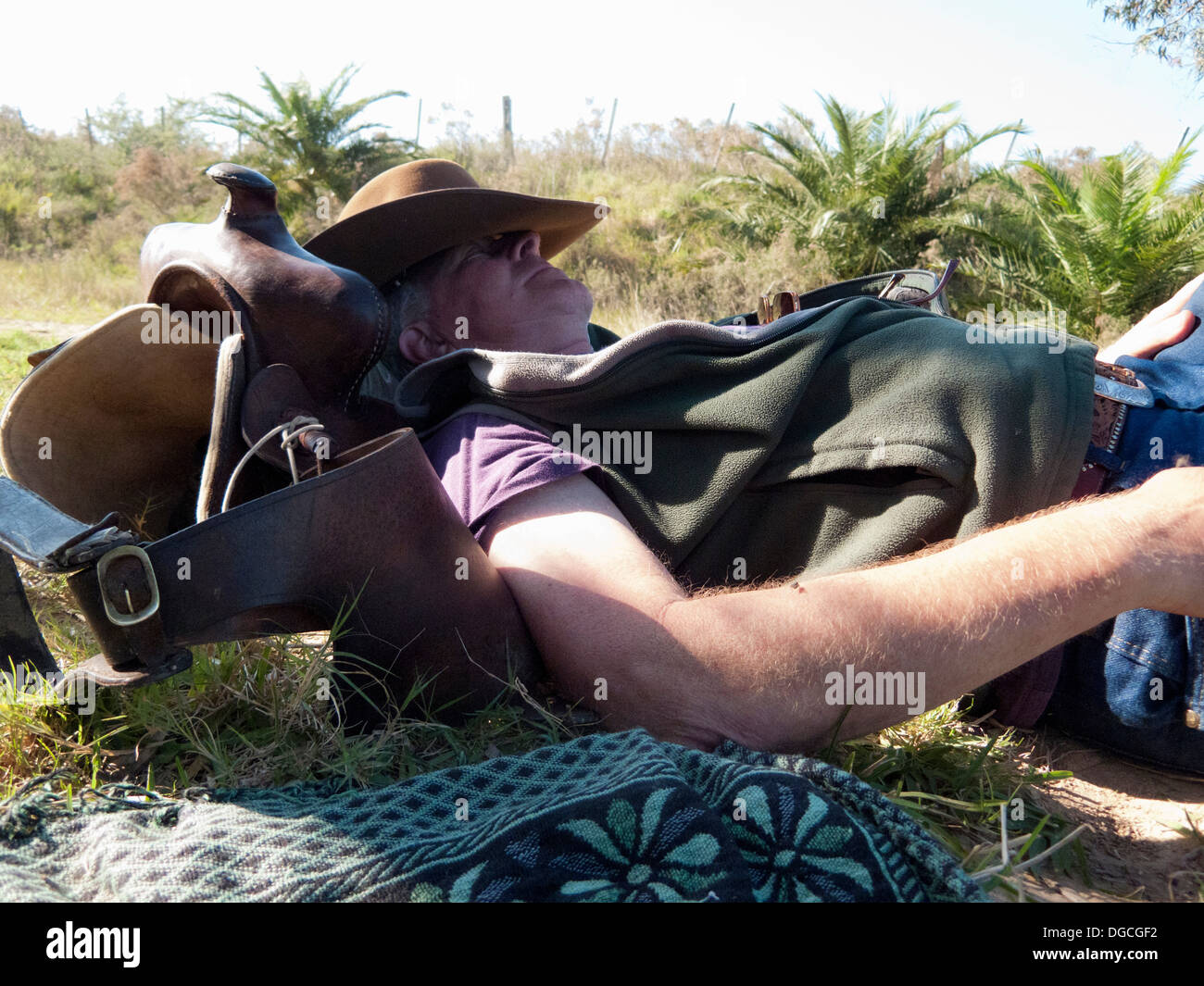 Senior man lying on back resting on saddle, Uruguay - Stock Image