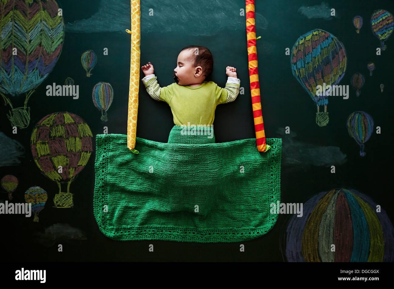 Baby girl sleeping against drawings on blackboard, overhead view - Stock Image