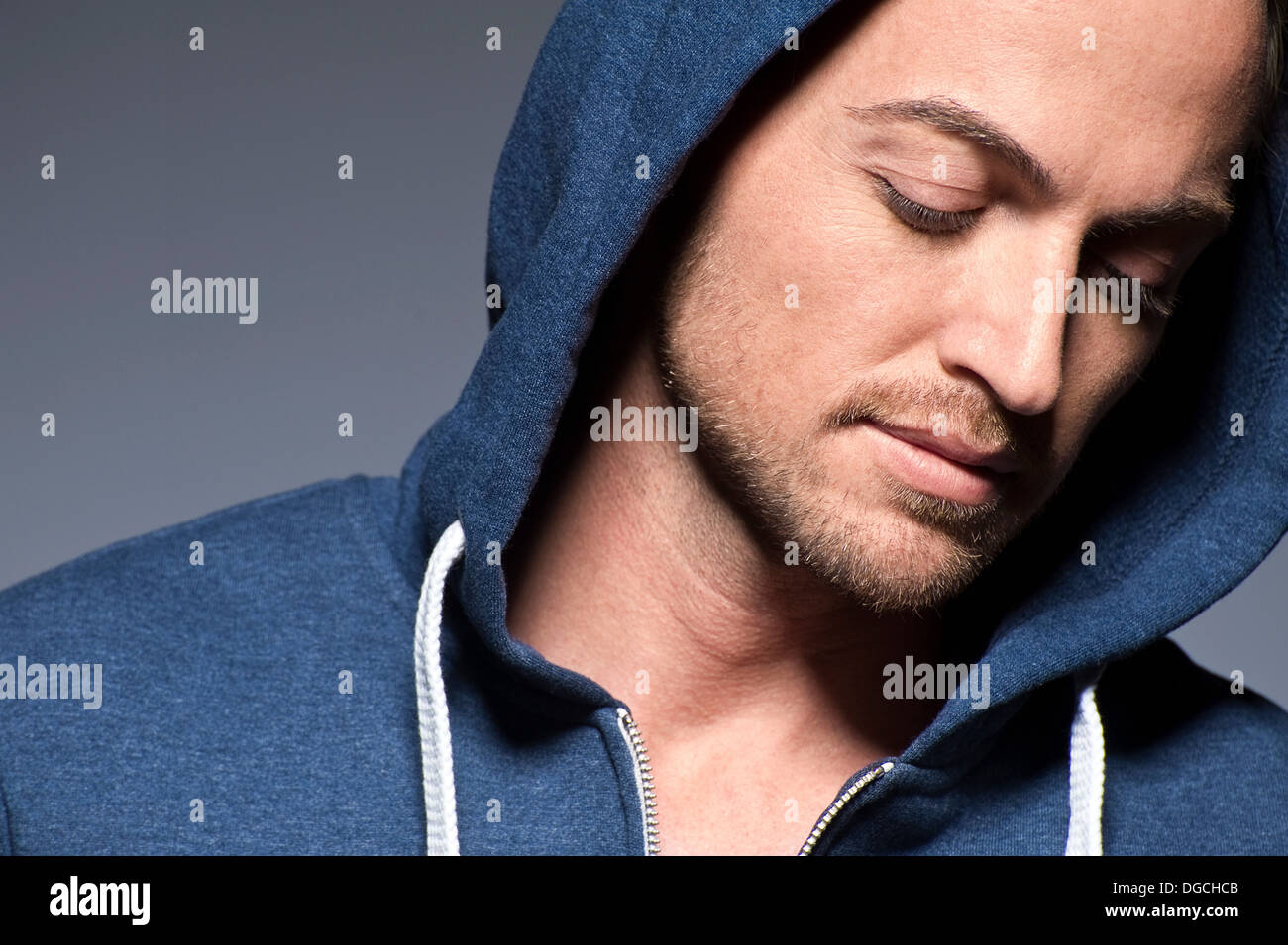 Young man wearing hood and looking down - Stock Image