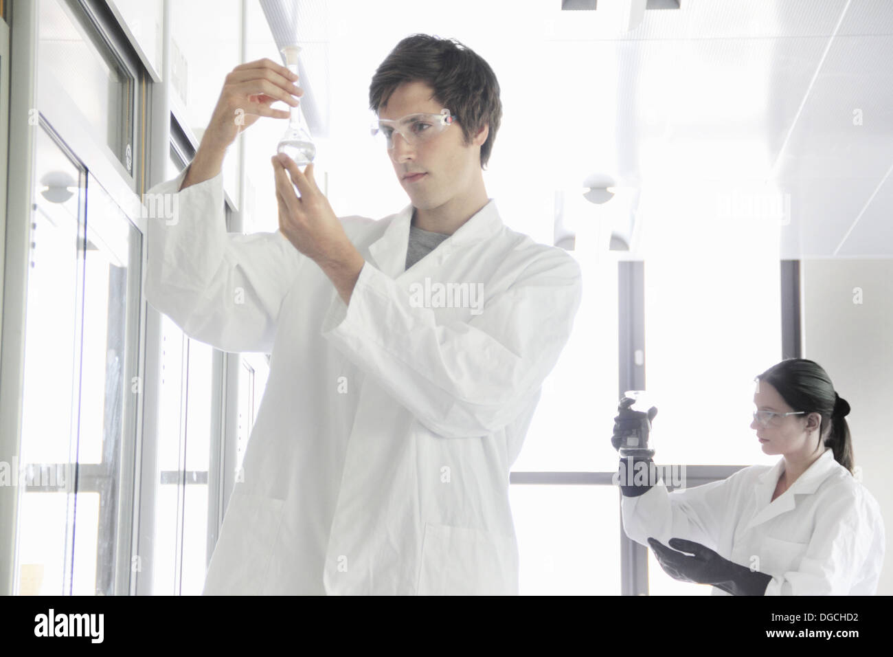 Chemistry students looking at chemicals in lab - Stock Image