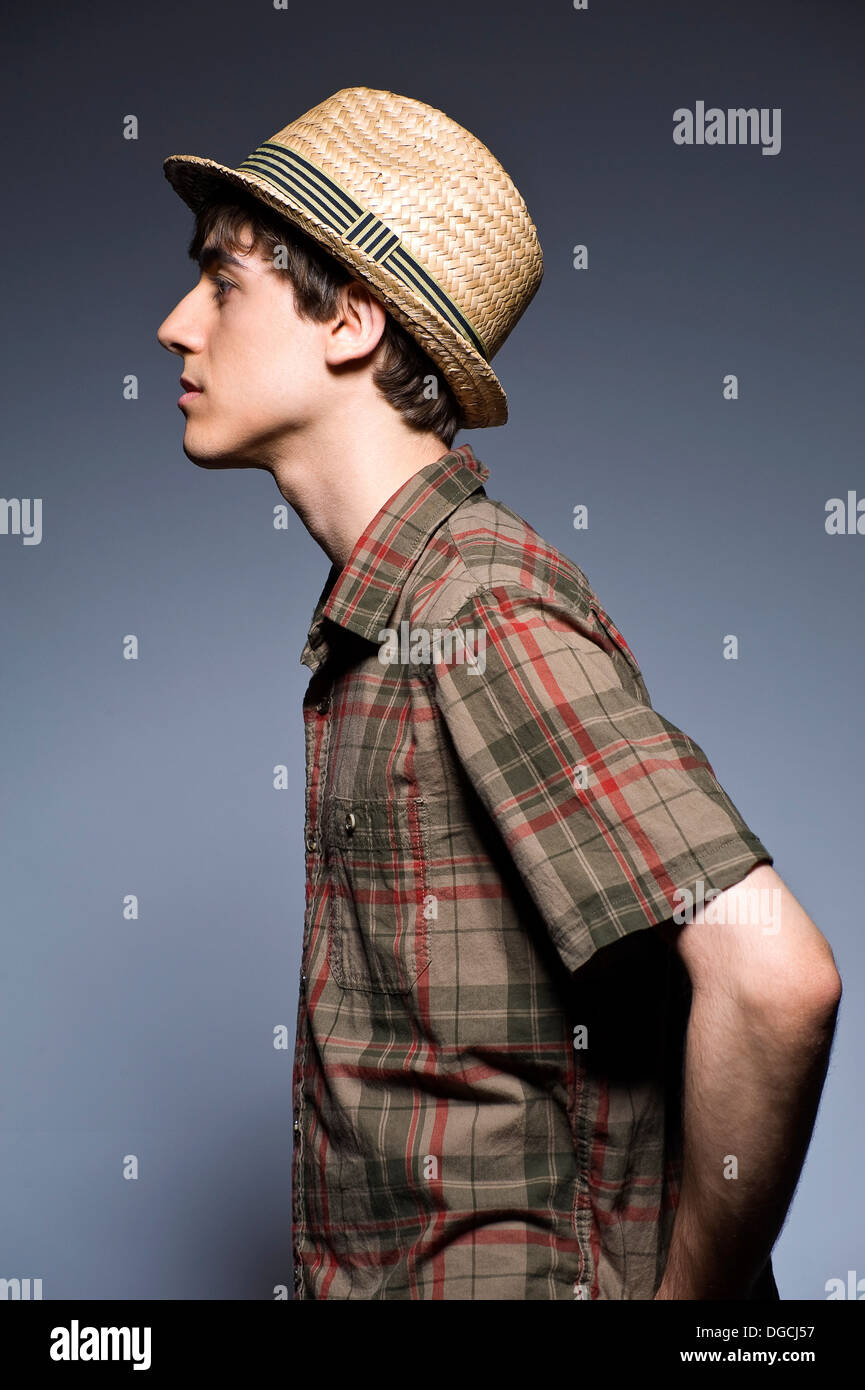 Young man wearing hat and short sleeved shirt, profile - Stock Image