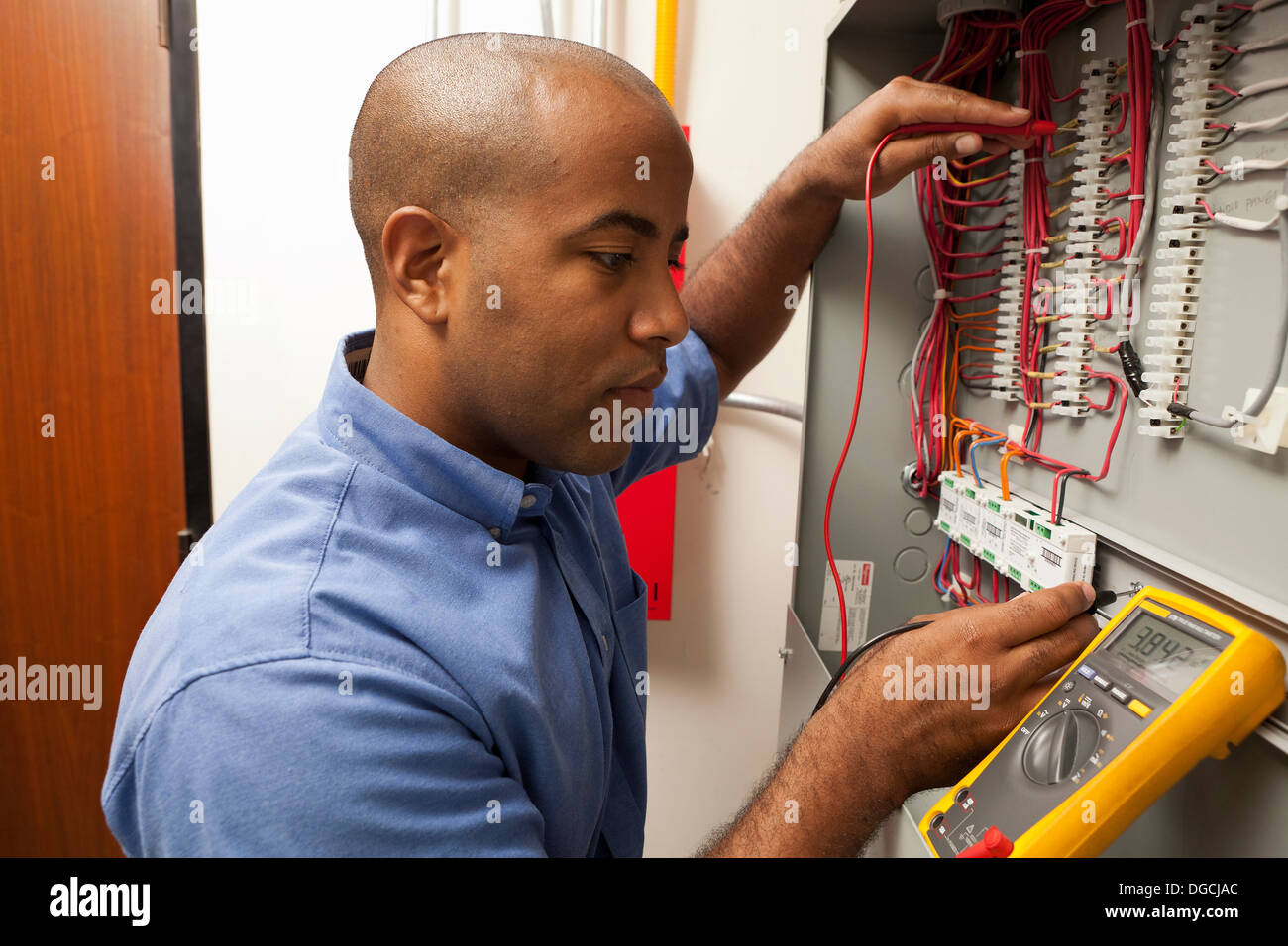 Mid adult electrical engineer working in manufacturing plant - Stock Image
