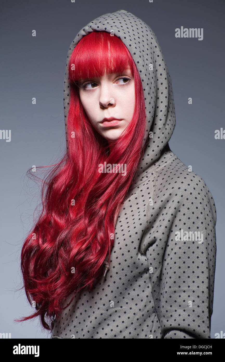 Young woman with long red hair in hooded top - Stock Image
