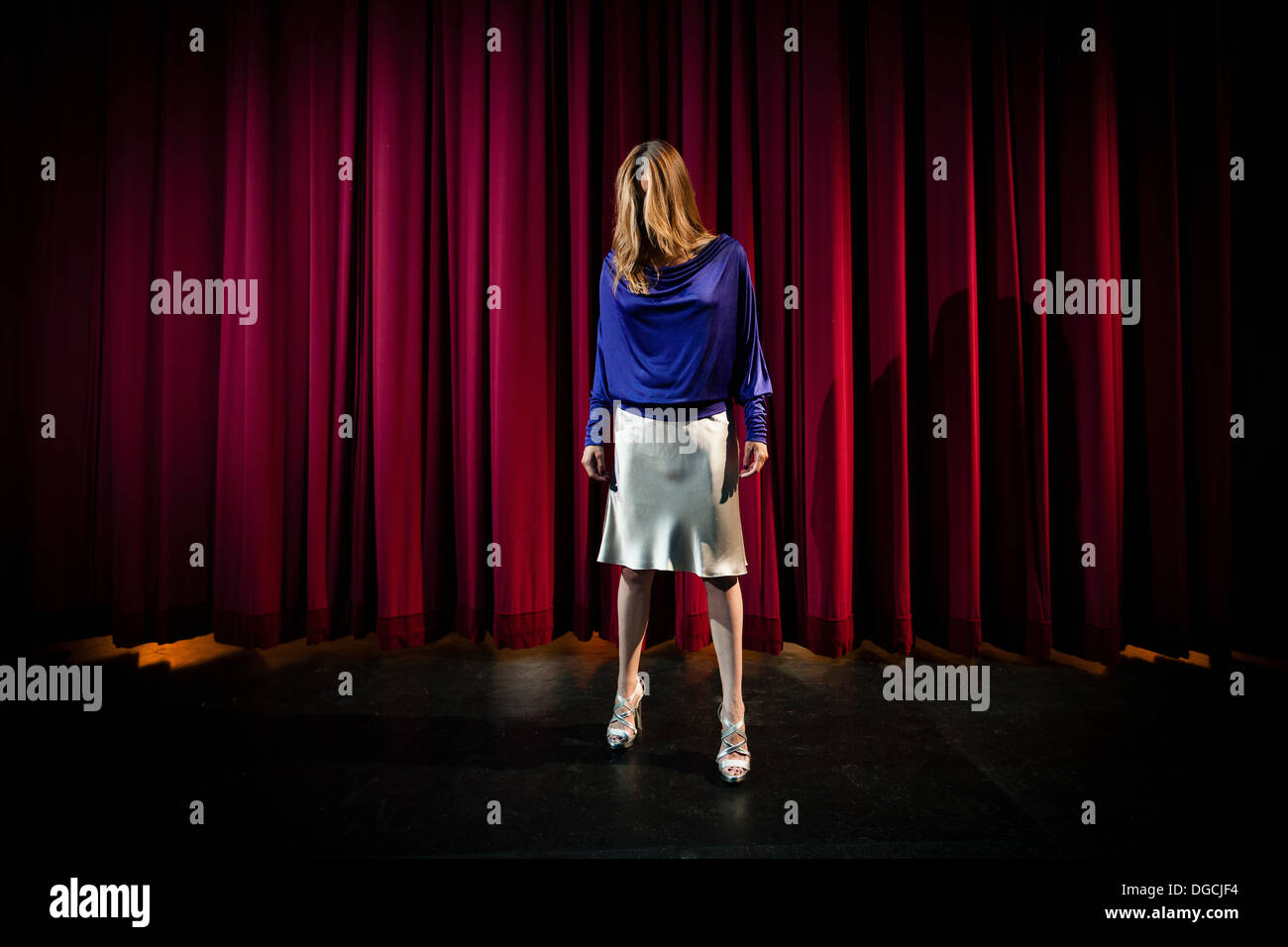 Mature woman standing in theatre stage with hair covering face Stock Photo