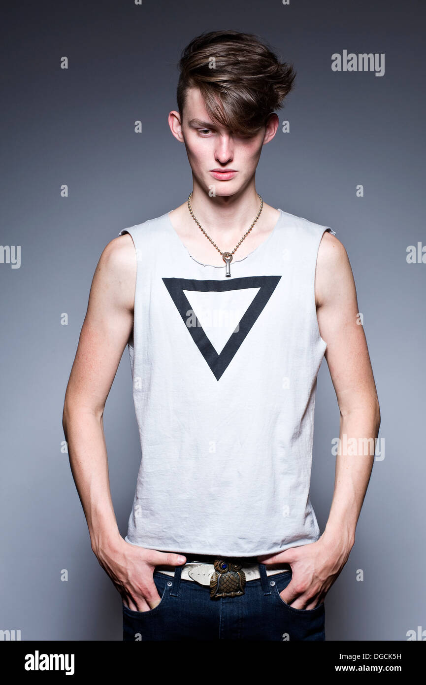 Young man in sleeveless t-shirt with hands in pockets - Stock Image