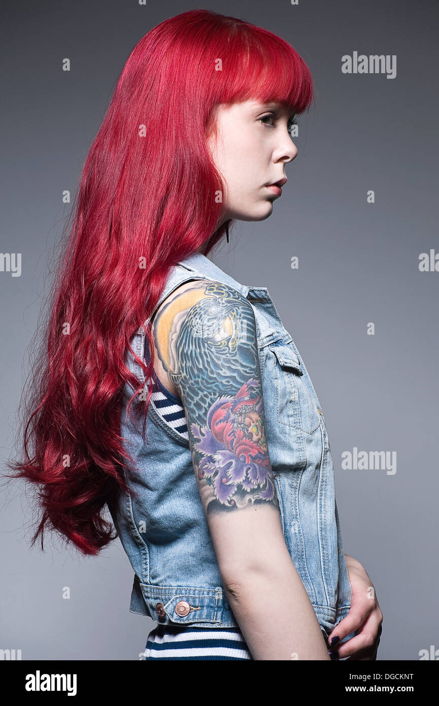 Young woman with long red hair and tattoos, profile - Stock Image