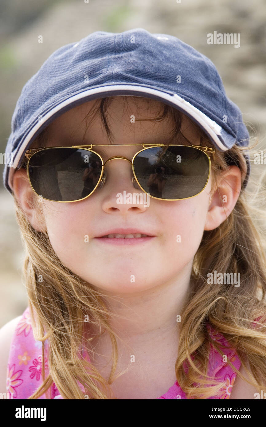 1d0c7dced3c4 5 year old girl wearing a baseball cap and her daddys sunglasses ...