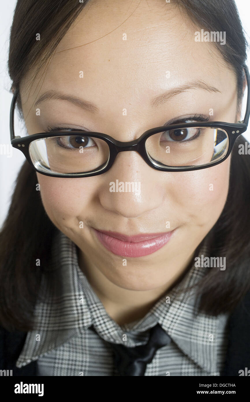 Portrait head shot of young Chinese Asian woman in her 20´s with glasses  and hair pulled back looking attentive alert