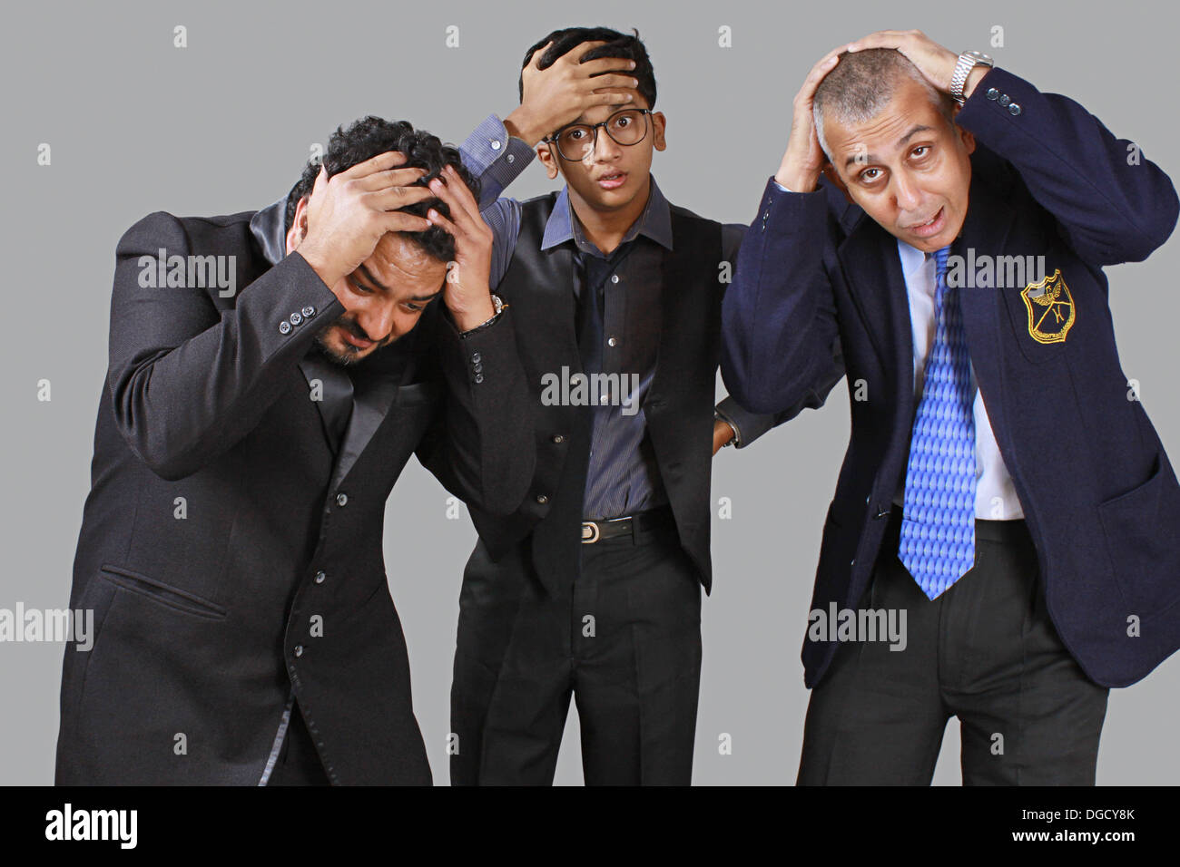 Three business men expressing sorrow over big loss in business - Stock Image
