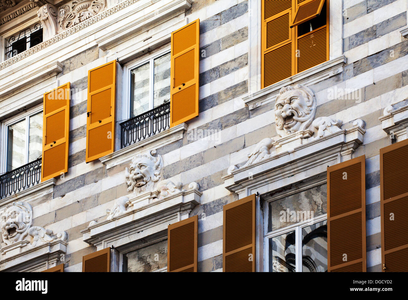 Stone Carved Faces and Shuttered Windows in Piazza di San Lorenzo Genoa Liguria Italy - Stock Image