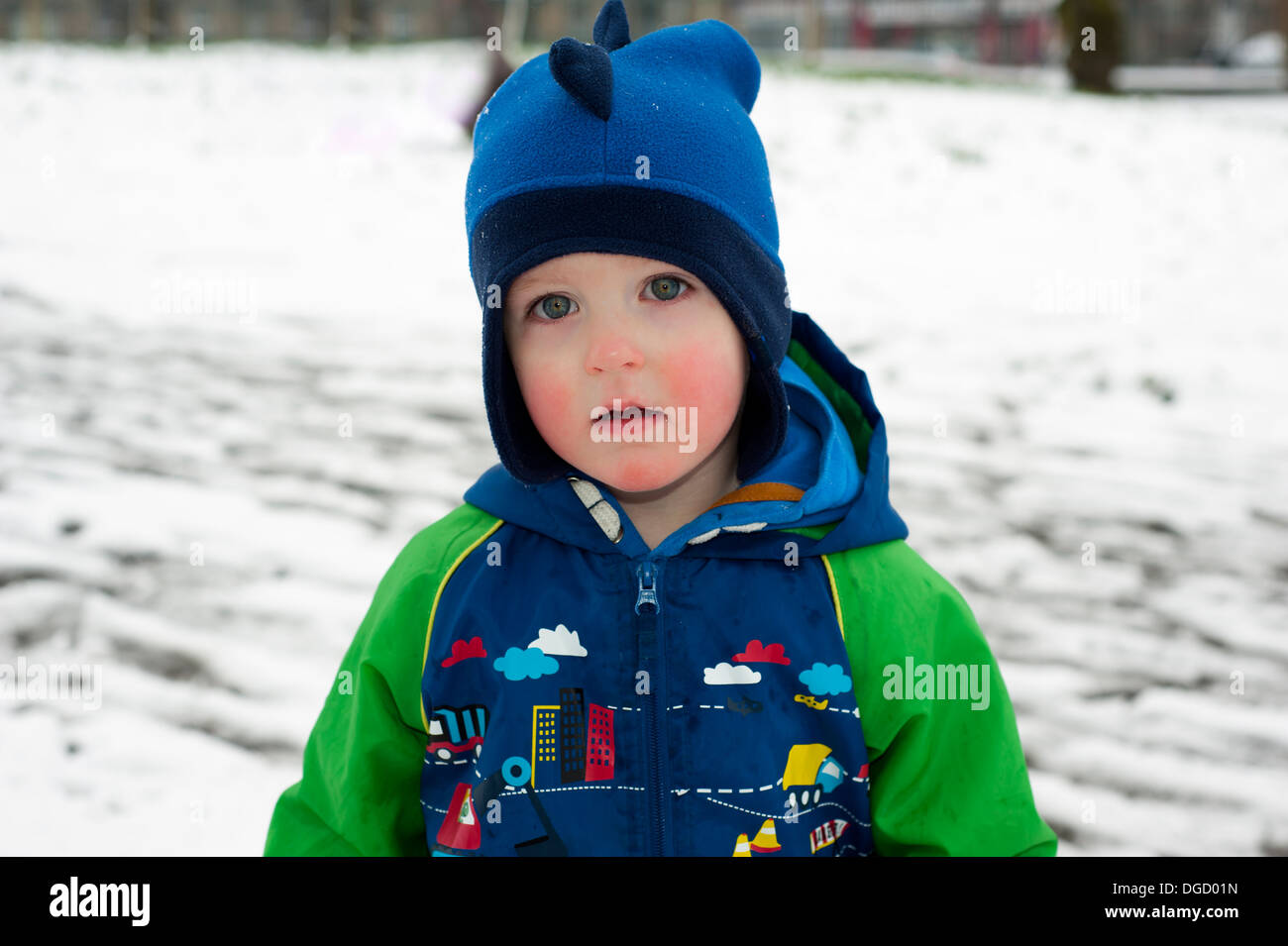 boy wearing woolly hat with red cheeks in snowy park - Stock Image