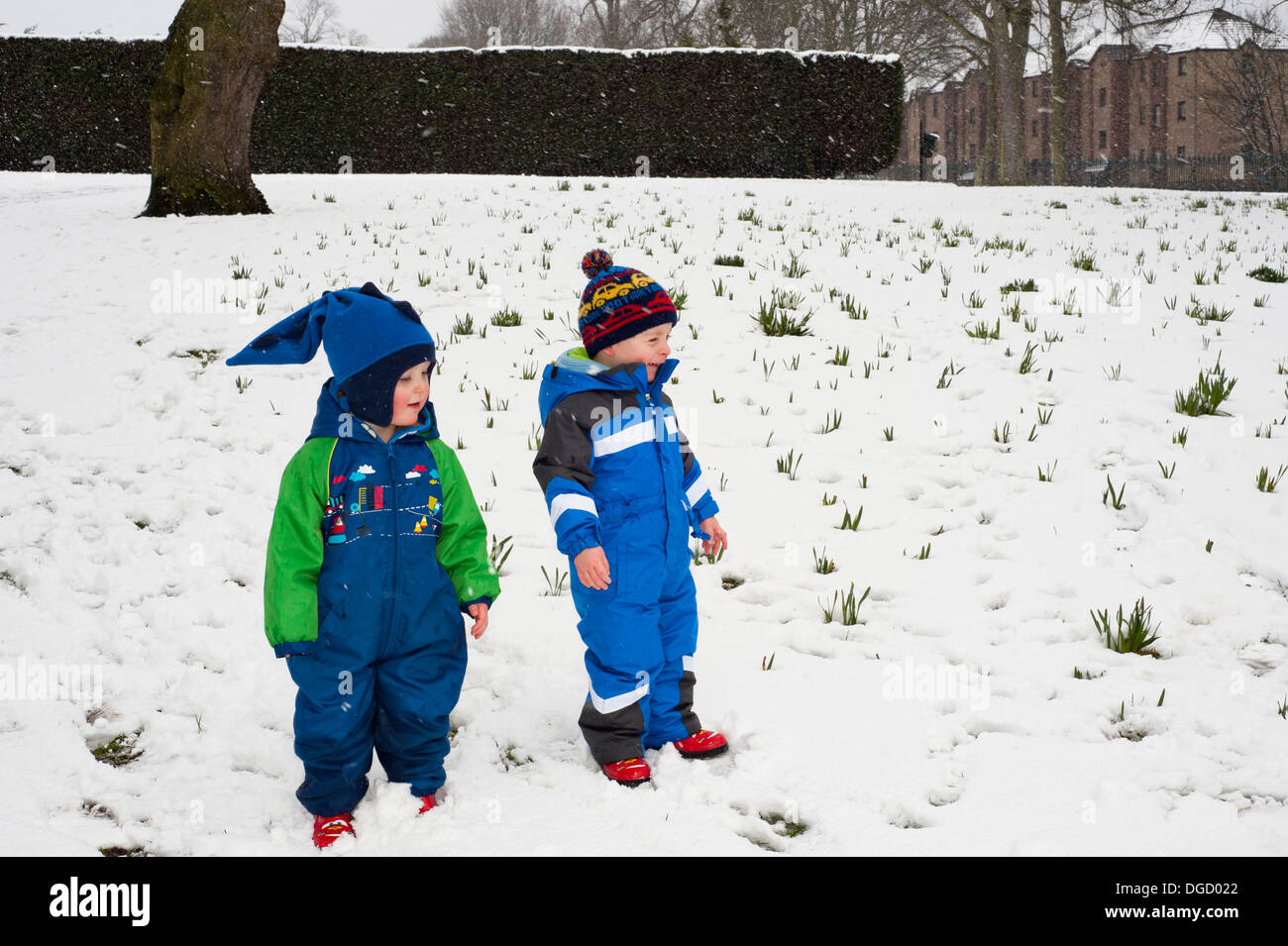 two toddlers having fun playing in park blizzard Stock Photo