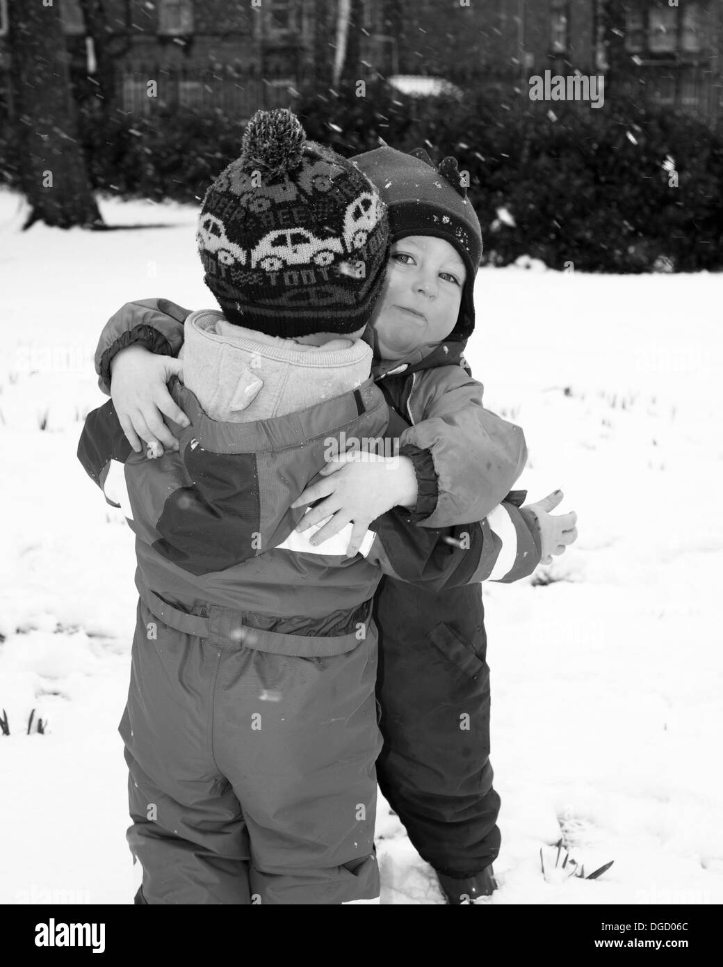 toddlers hugging in the snow Stock Photo