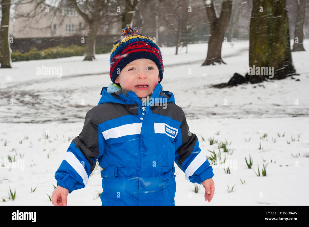 Young boy in snow blizzard looking cold - Stock Image