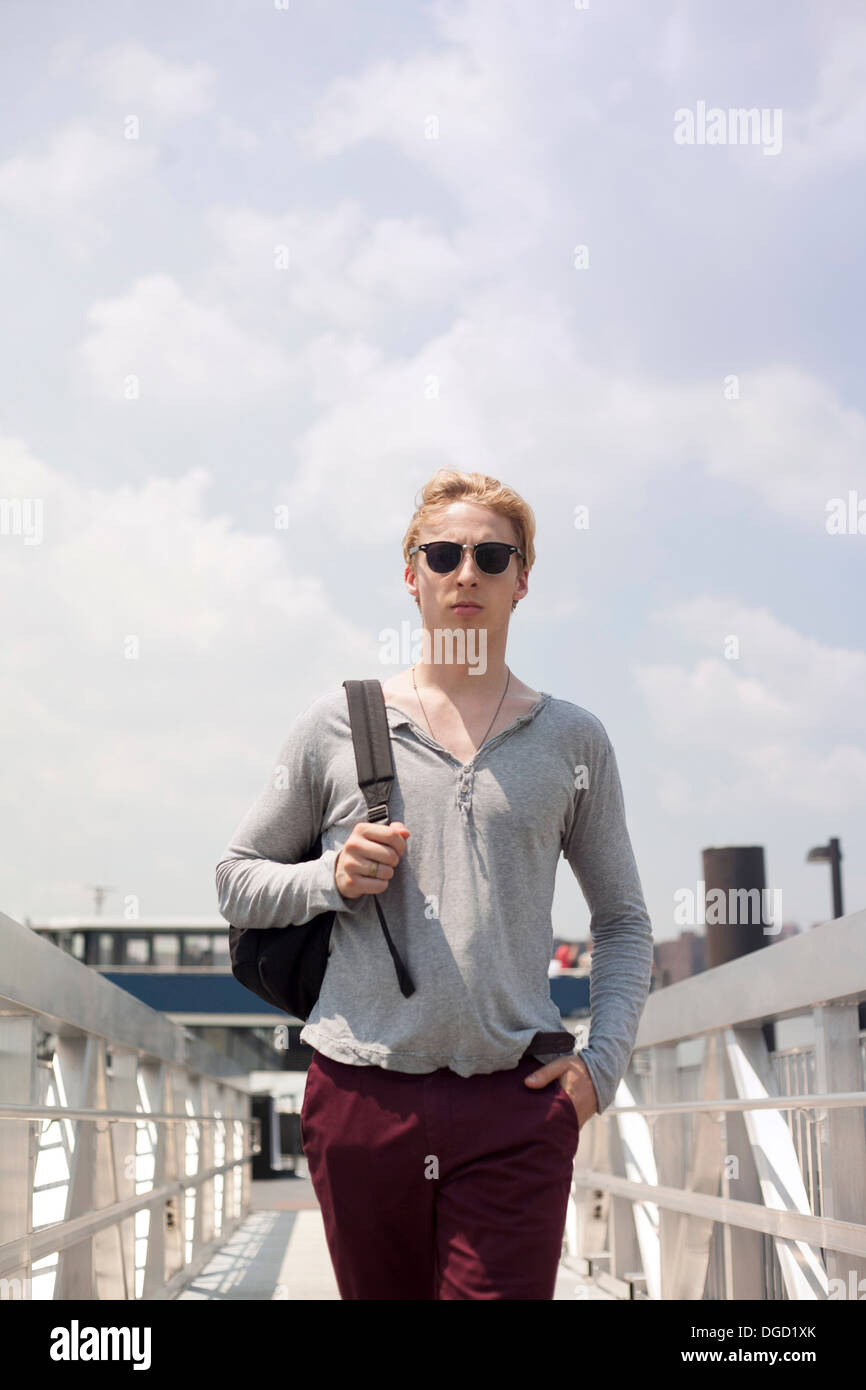 Young man walking over footbridge, Brooklyn, New York City, USA - Stock Image
