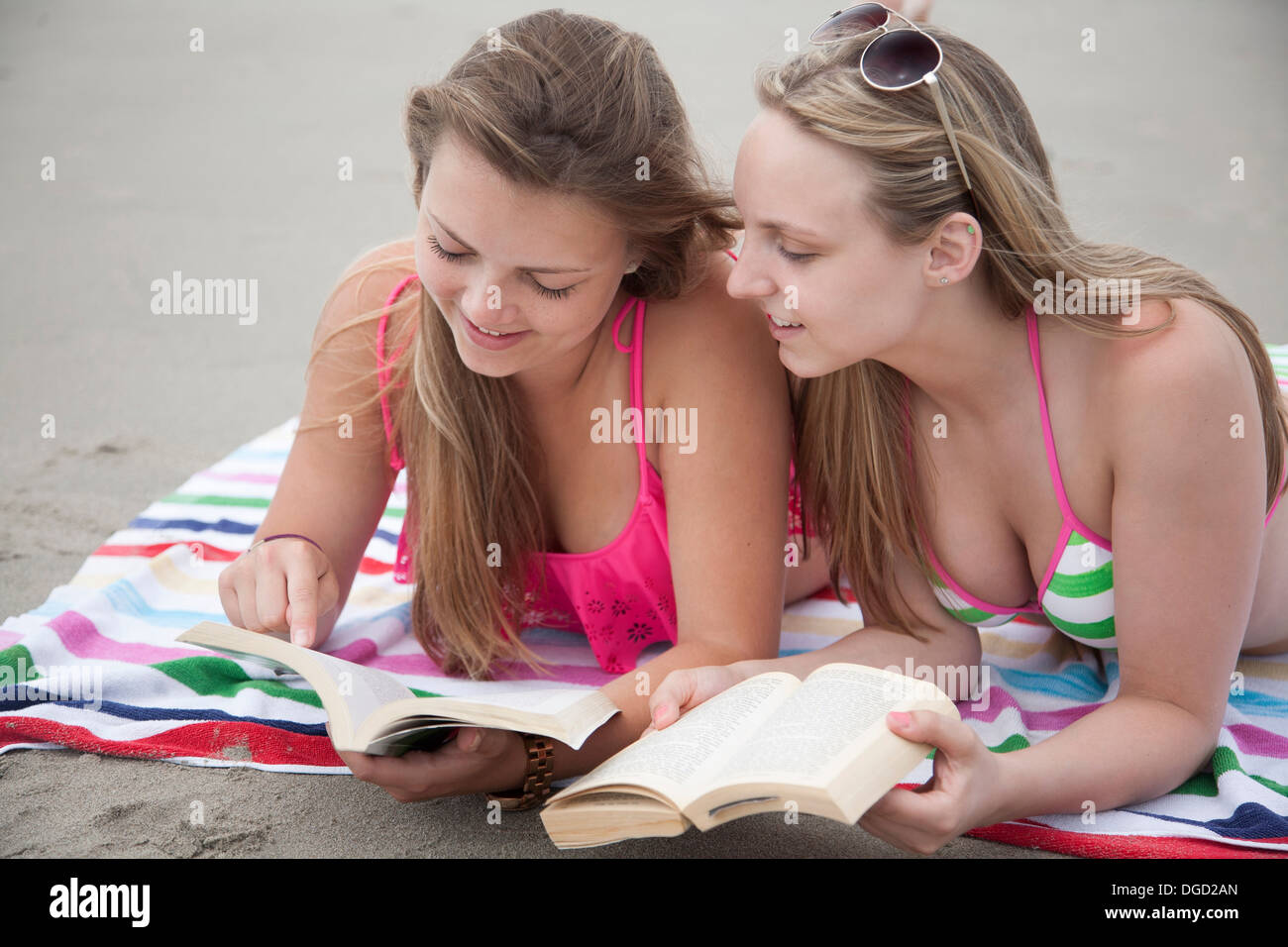 Young women reading books on beach - Stock Image