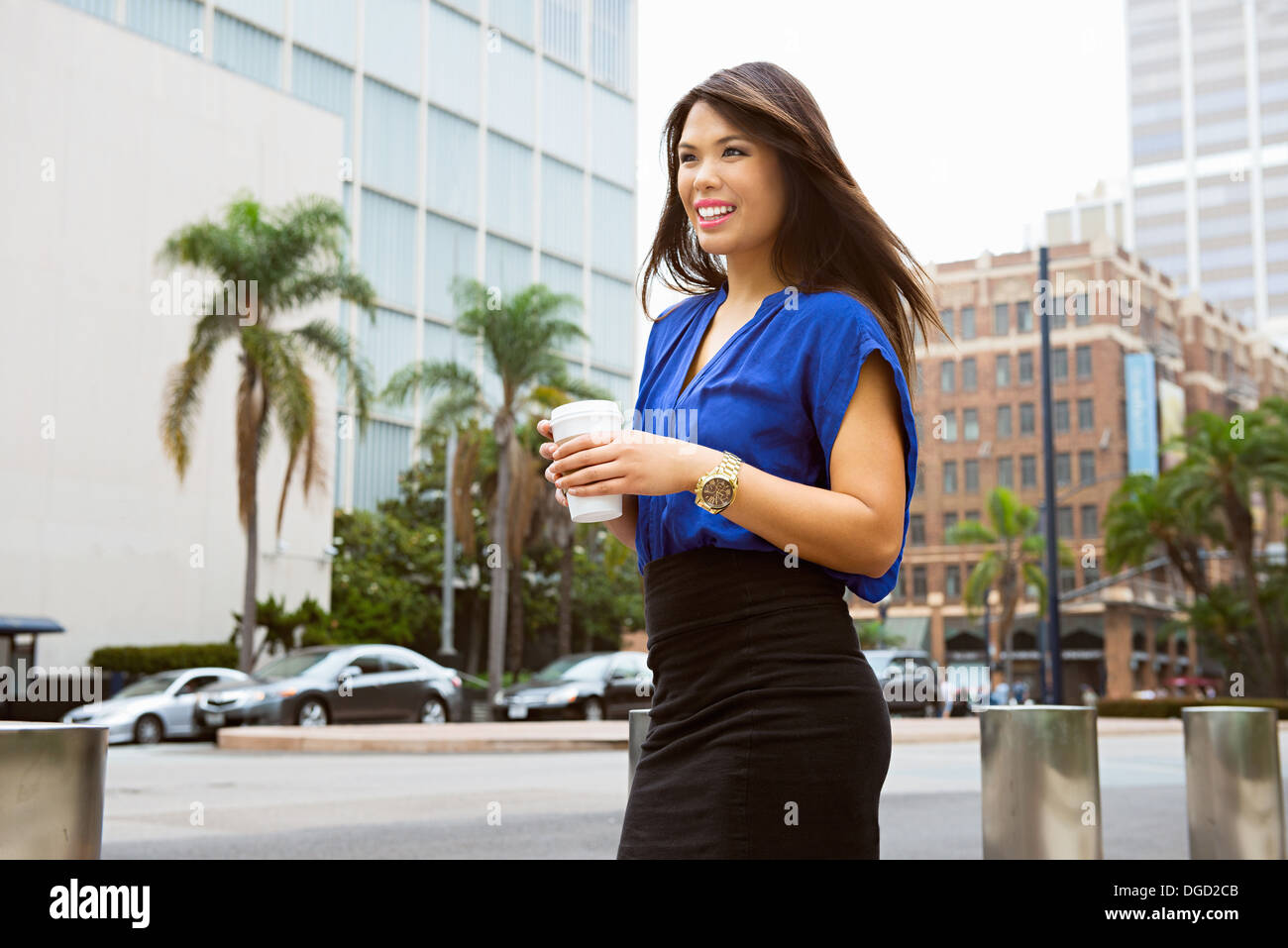 Young woman holding disposable cup in city, smiling - Stock Image