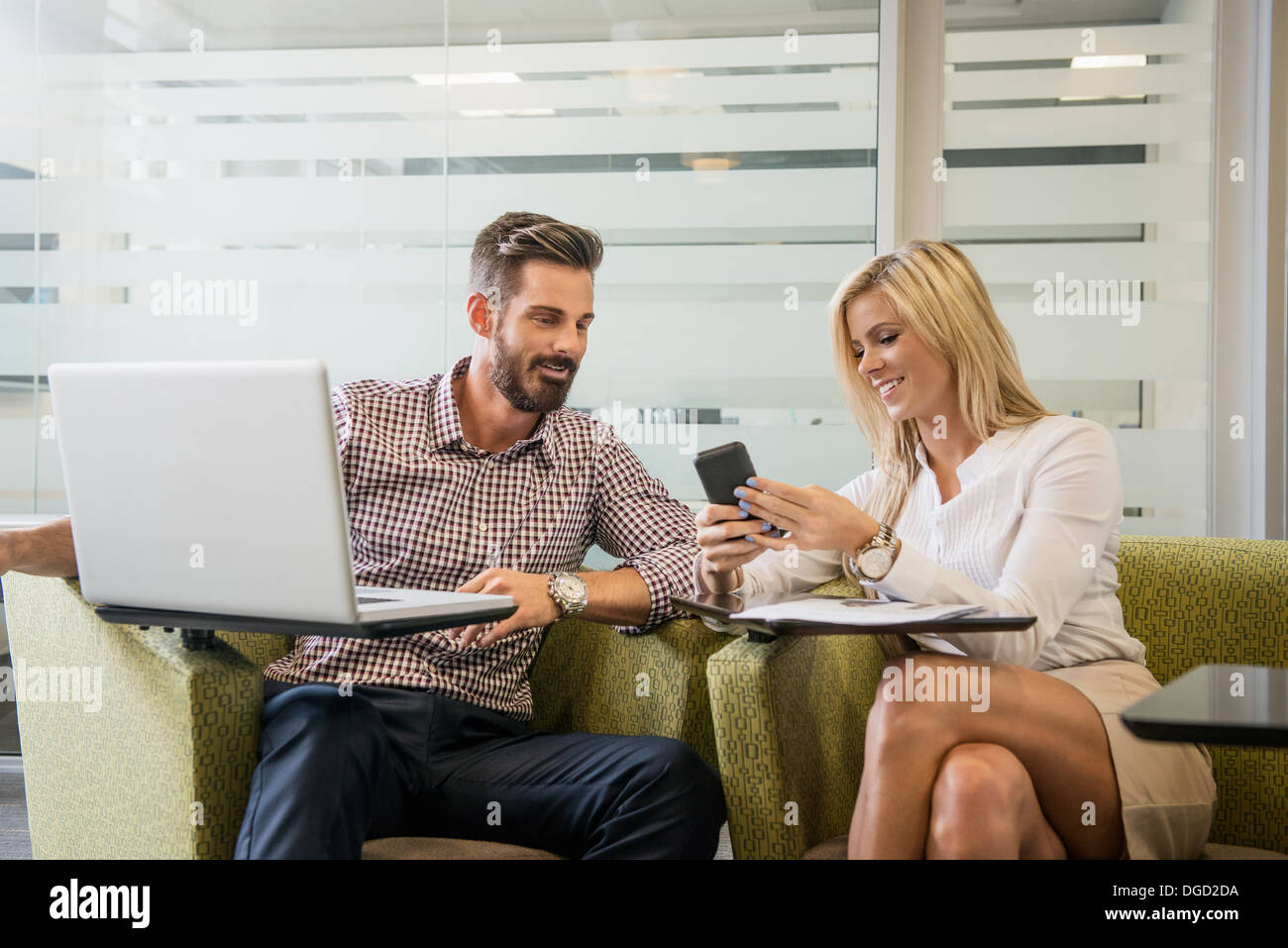 Young business colleagues looking at smartphone in meeting - Stock Image