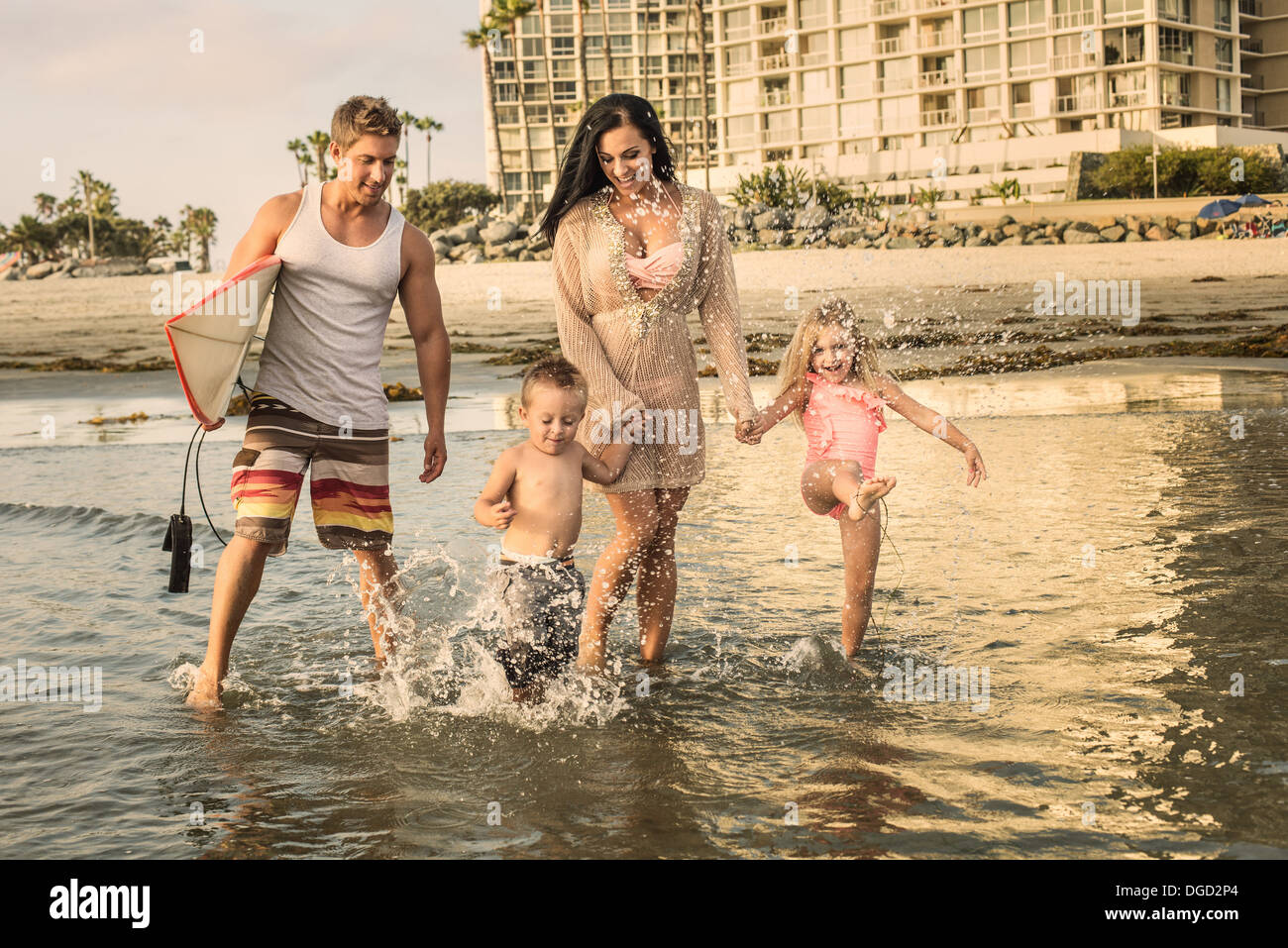 Young family paddling through water - Stock Image
