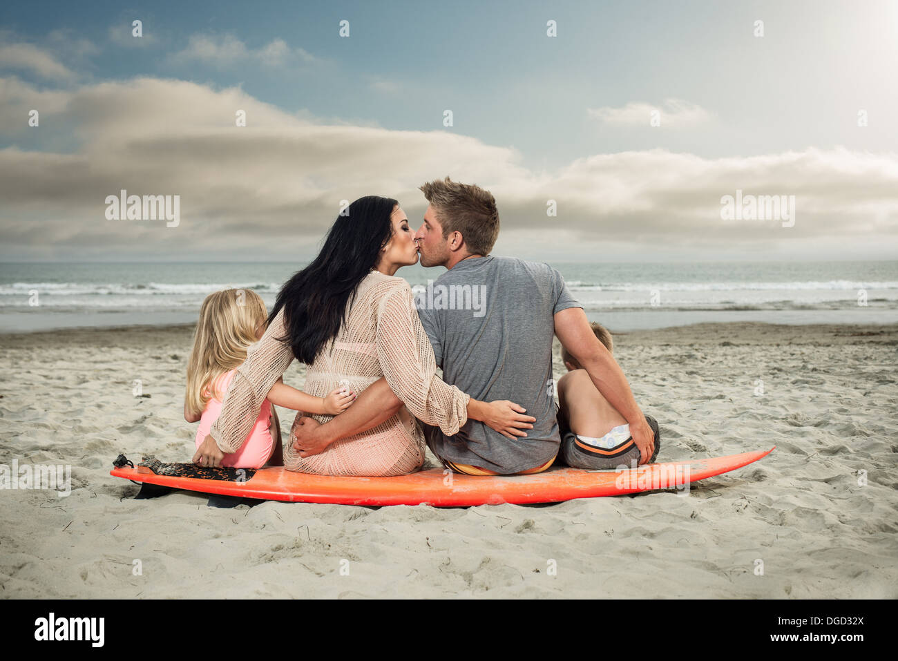 Young family sitting on surfboard on beach with parents kissing - Stock Image