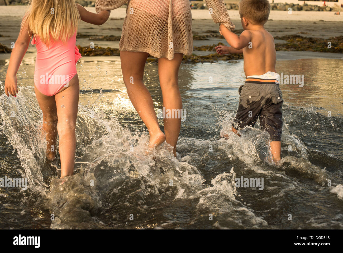Young family paddling through water, rear view - Stock Image