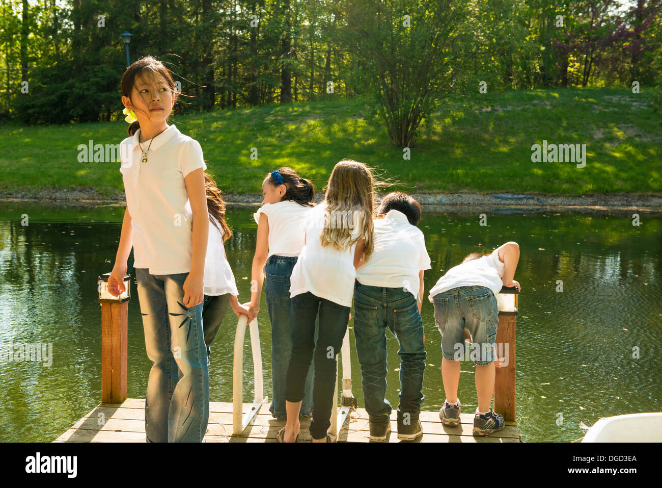 Children on jetty by lake - Stock Image