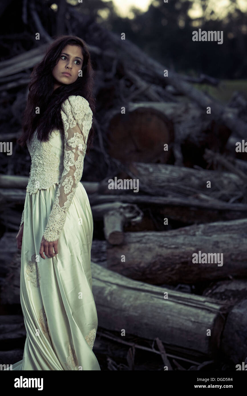 Woman in wedding dress standing in front of cut down trees - Stock Image