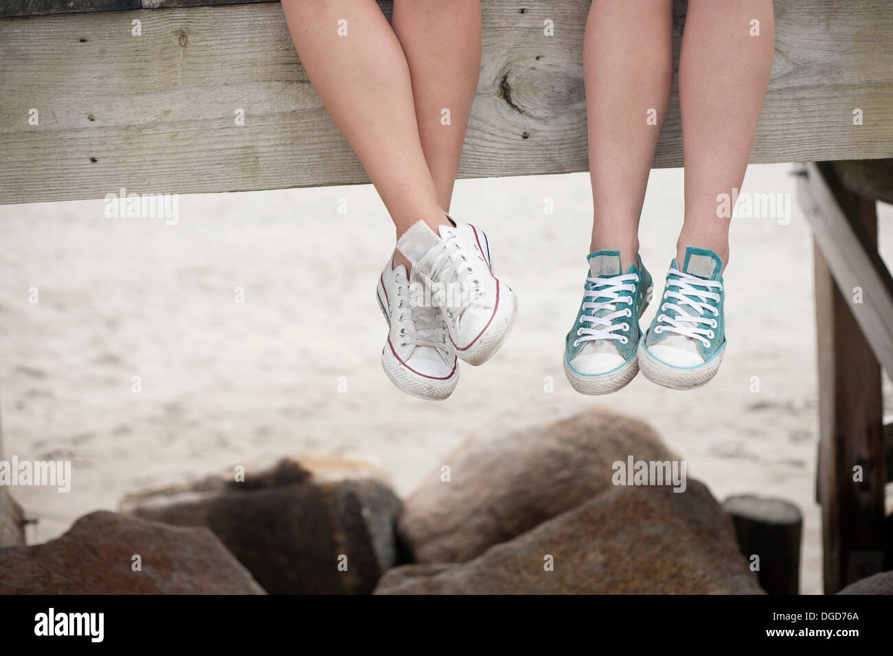 Young women sitting on pier on beach, low section - Stock Image