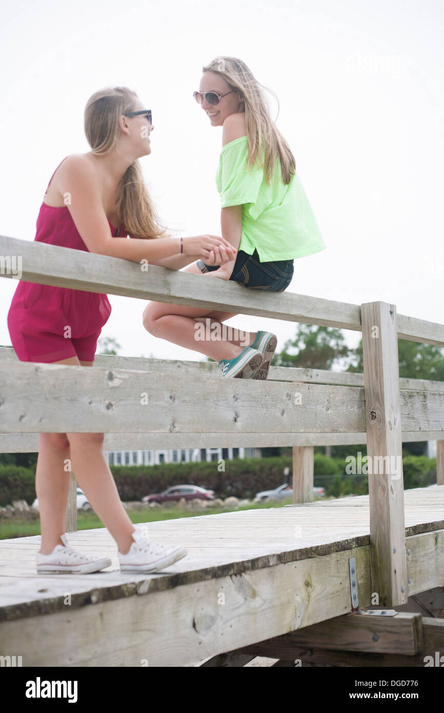 Young women standing and sitting on pier Stock Photo