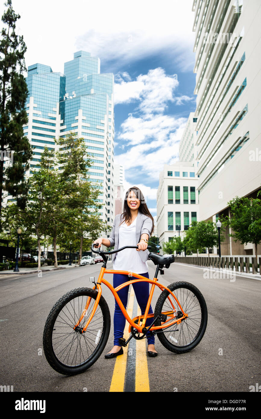 Young woman standing road with bicycle in city, smiling Stock Photo