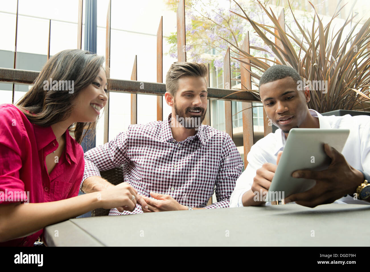 Young business colleagues looking at digital tablet in meeting - Stock Image