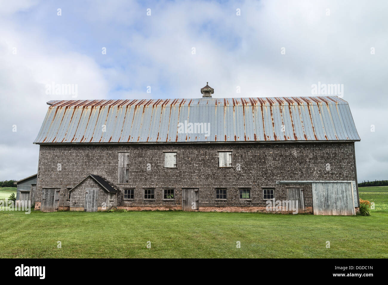 Old weathered shake shingle sided barn with rusted metal roof Prince Edward Island, one of the Maritime Provinces in Canada. - Stock Image