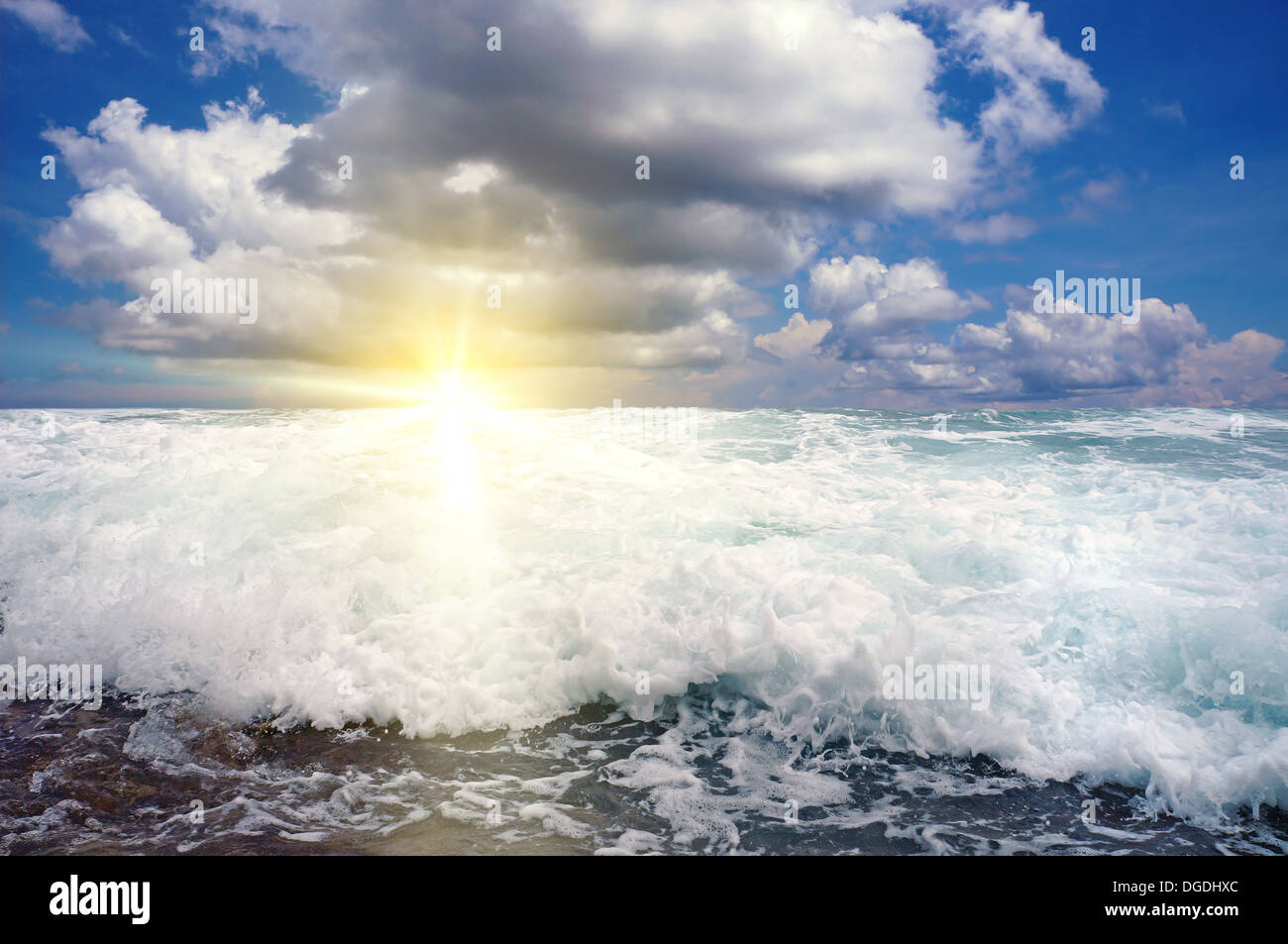 Breaking wave with sunset light and cloudy sky - Stock Image