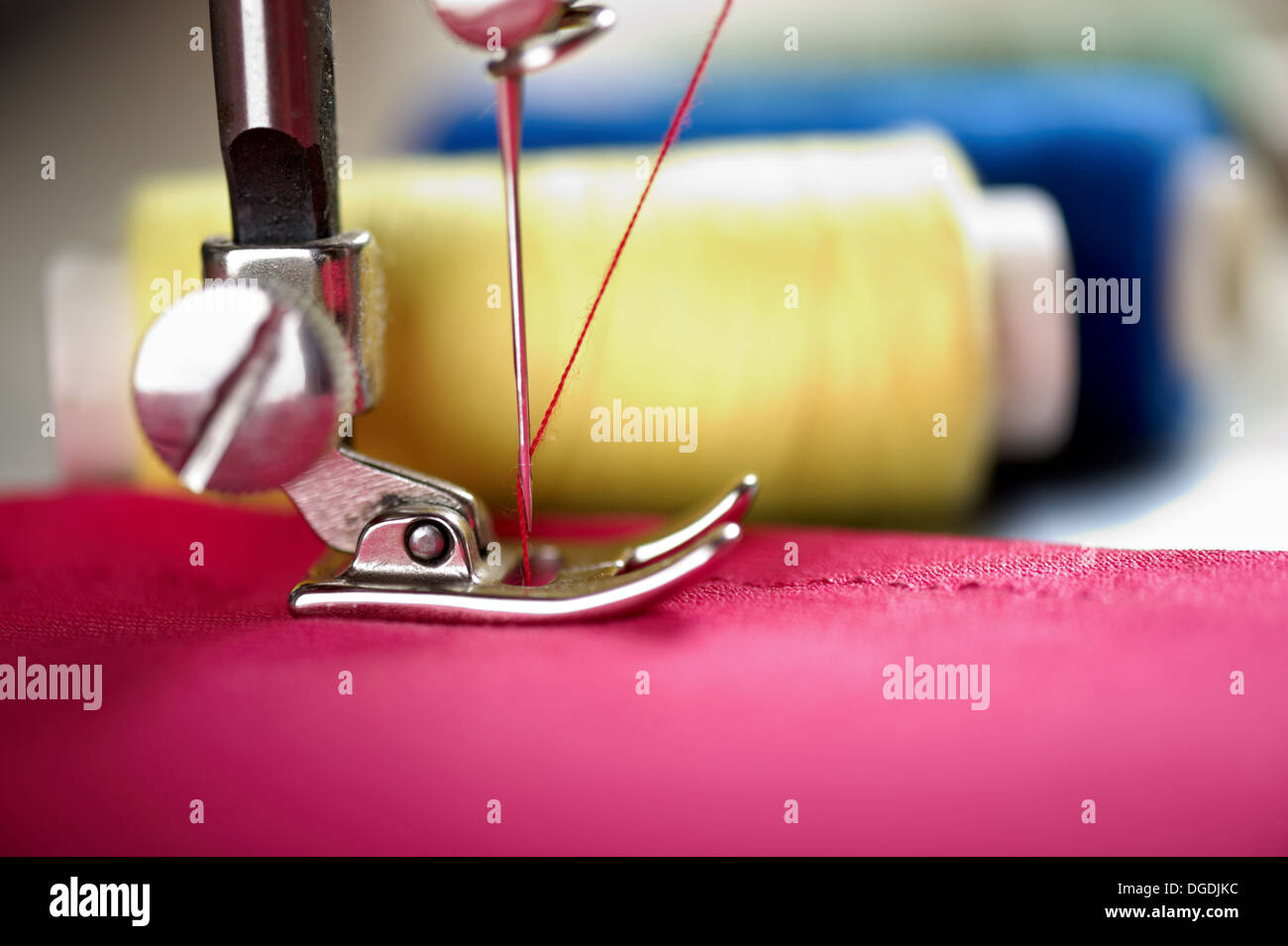 Close up of threads on fabric and sewing machine. Shalow DOF. Selective focus. Focus on blue threads. - Stock Image