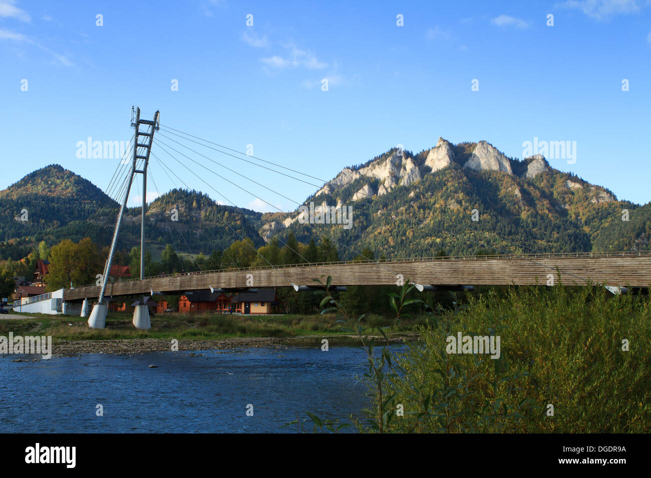 Suspension footpath bridge between Poland and Slovakia over Dunajec river in Pieniny mountains. Trzy Korony peak in background. - Stock Image