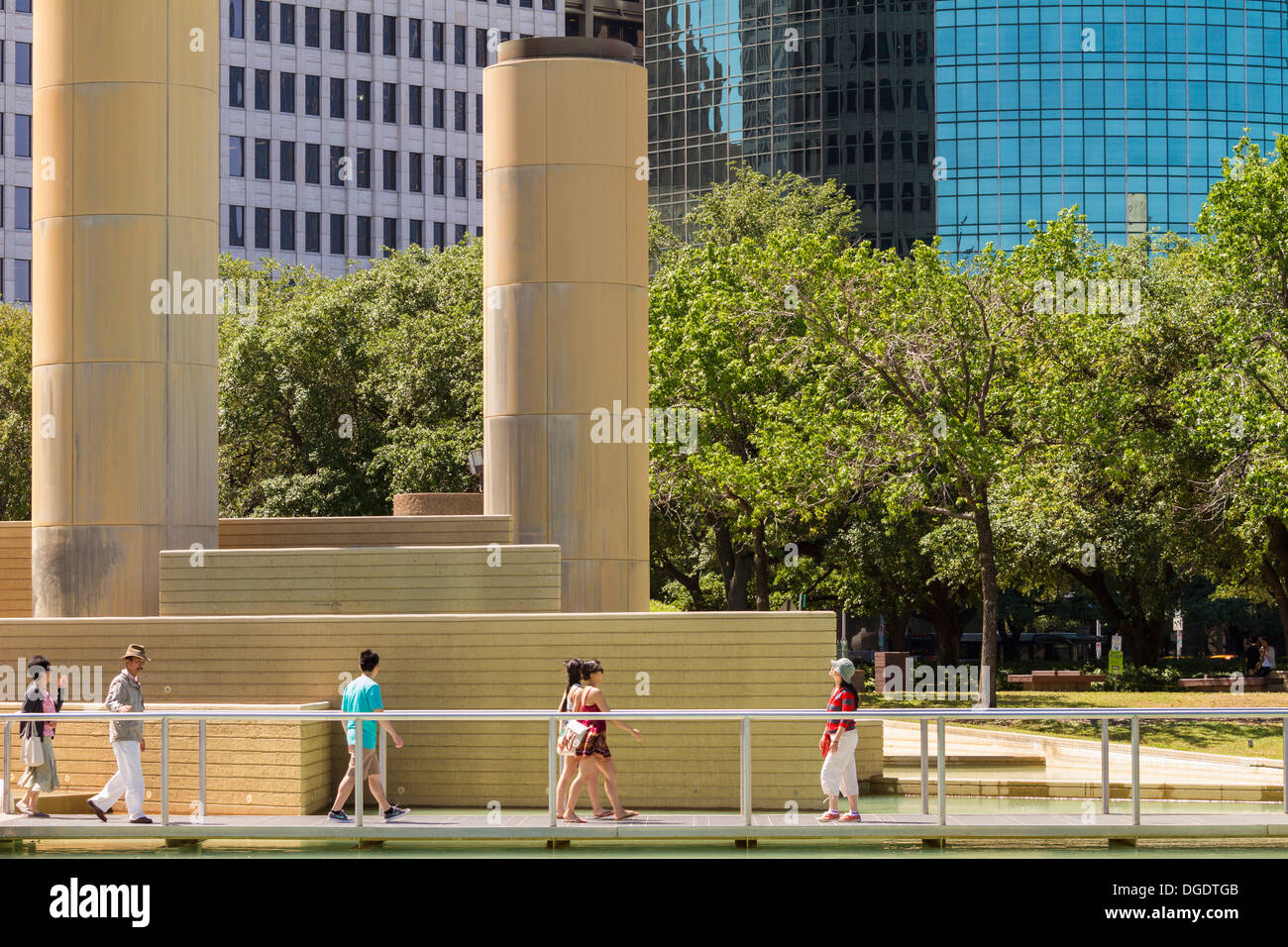 People walk through Tranquillity Park in front of Houston skyscrapers on a sunny day - Stock Image