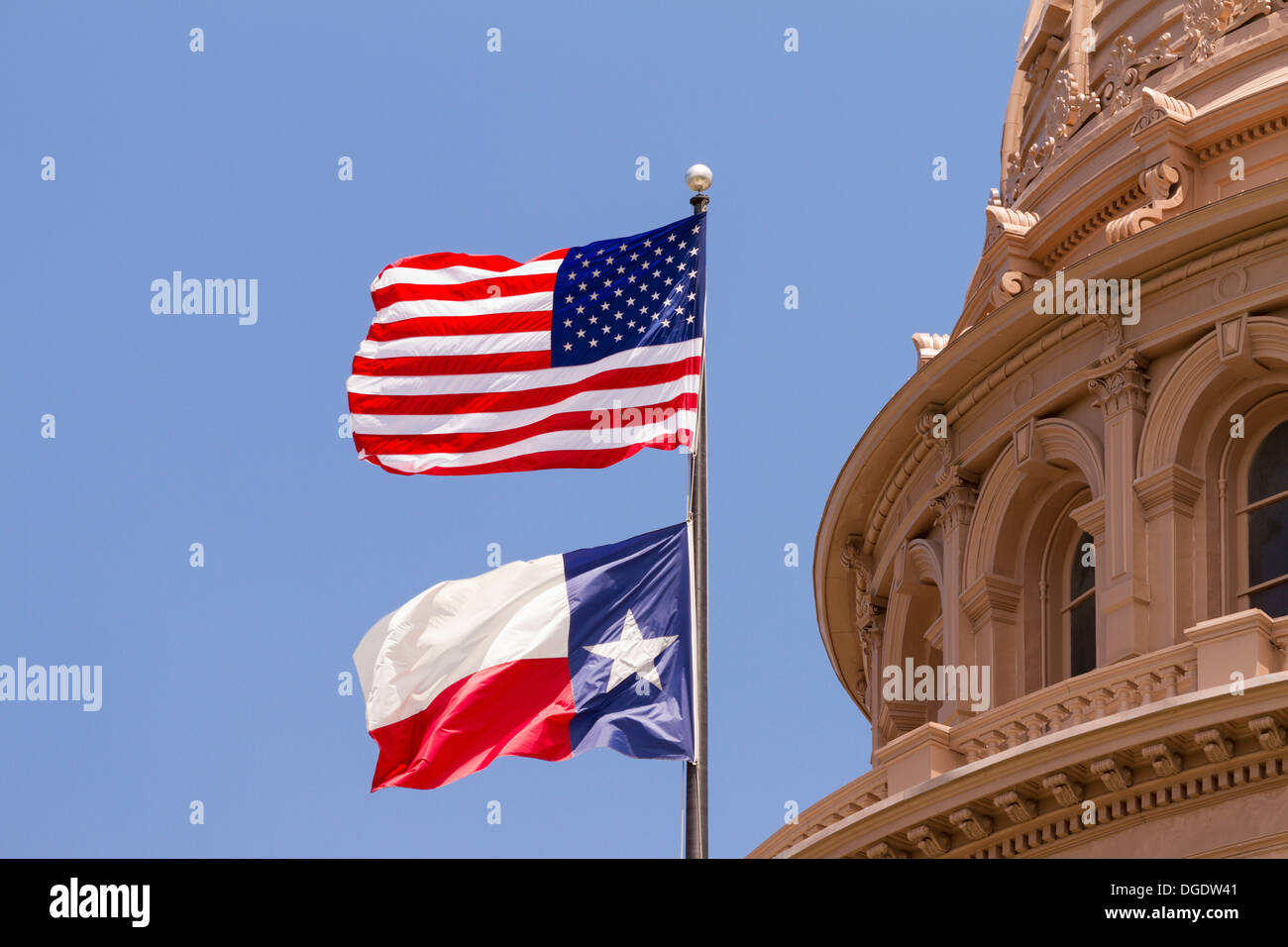 US and Texas flags flying over Texas State Capitol building Austin USA Stock Photo