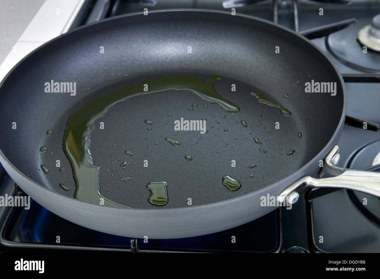Olive oil heating in frying pan on stove - Stock Image