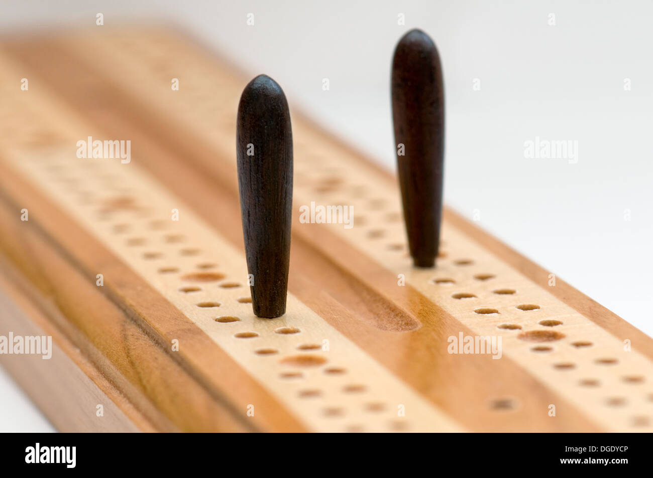 Two pegs on wooden cribbage board used for scoring in a crib card game - Stock Image