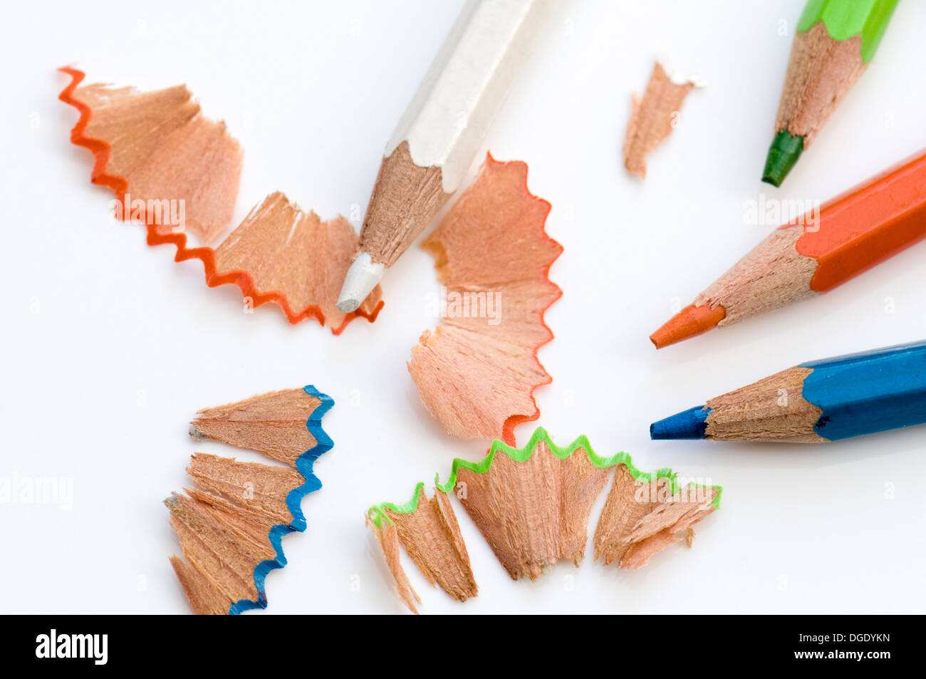 Colouring pencils with pencil shavings on old white background - Stock Image