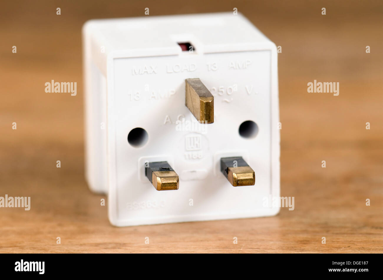 3 way plug adaptor 13 amp on wooden table top - Stock Image