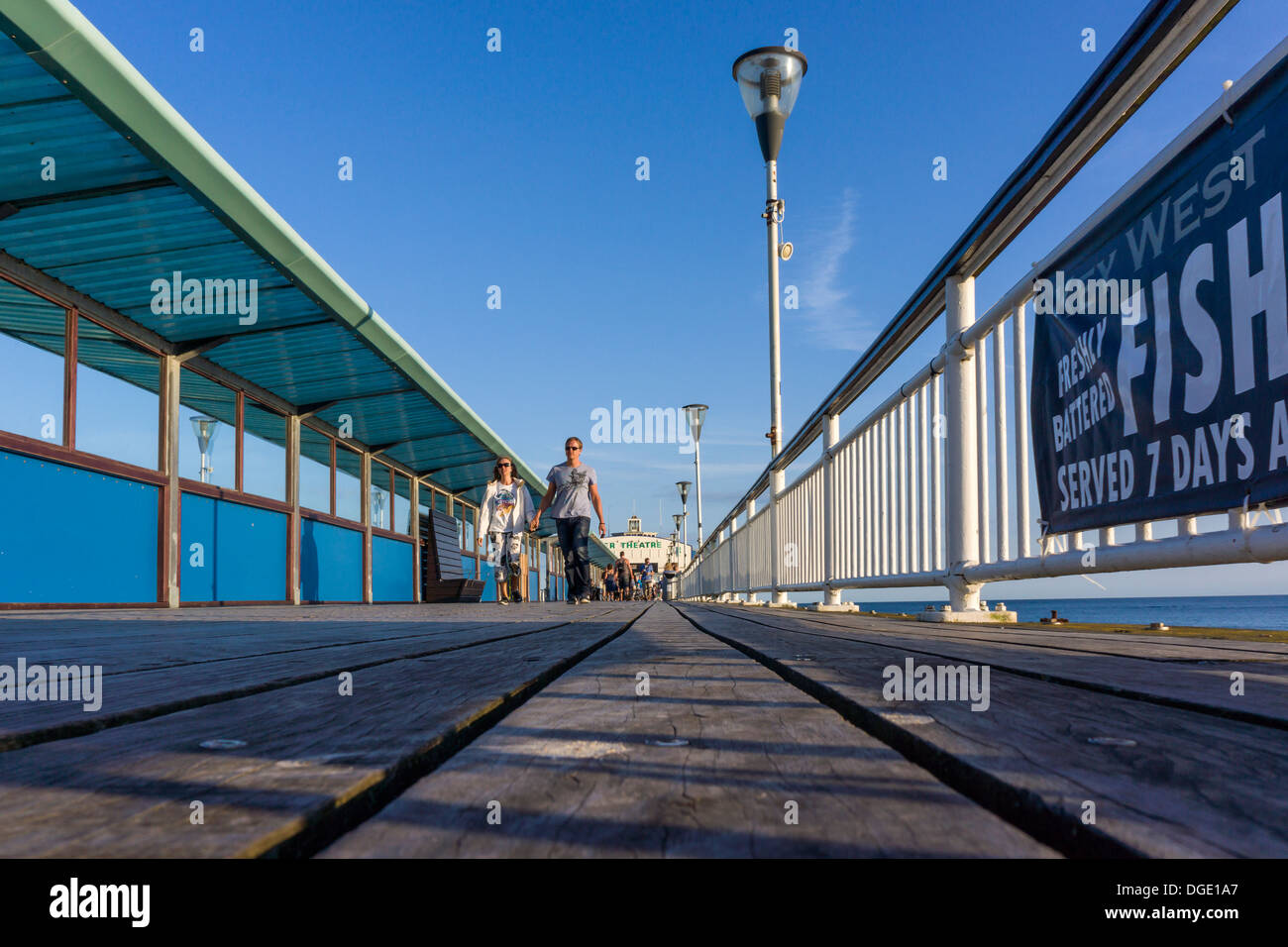 People walk along the pier at Bournemouth on a hot day in August at the height of the UK holiday season. - Stock Image