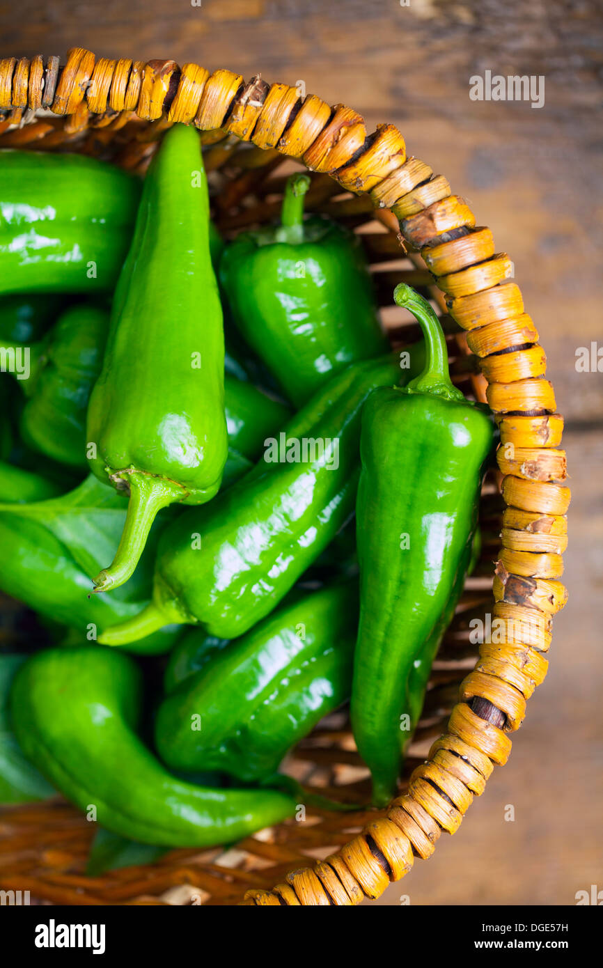 Green peppers in the wooden basket - Stock Image