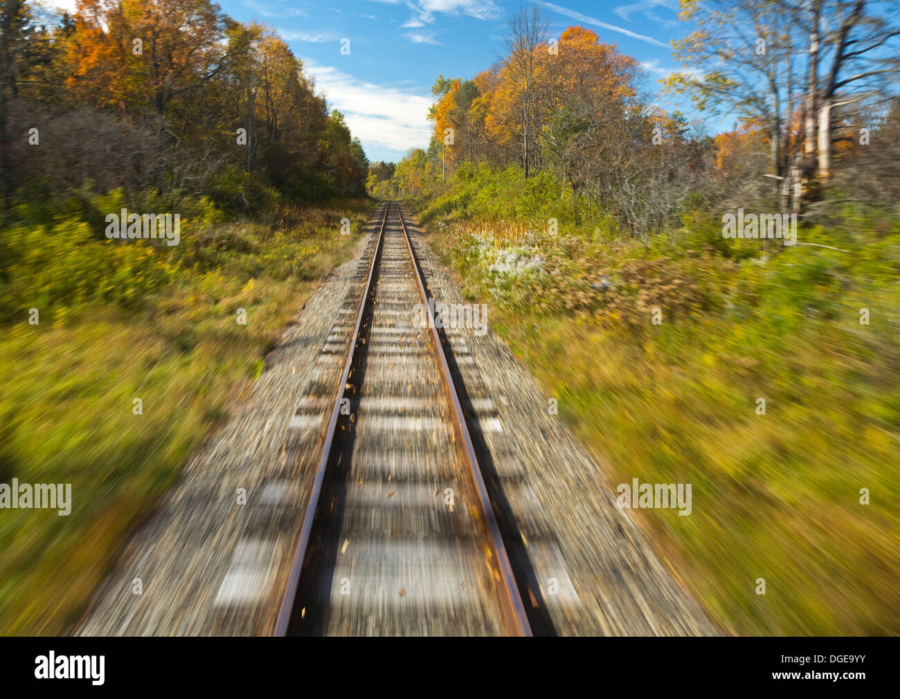 Train tracks in motion blur with autumn scene in background - Stock Image